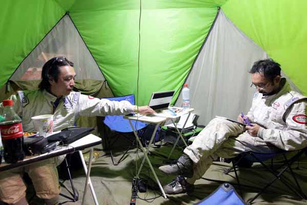 Teruhito Sugawara and Seiichi Suzuki discussing tomorrow's rally in the tent.